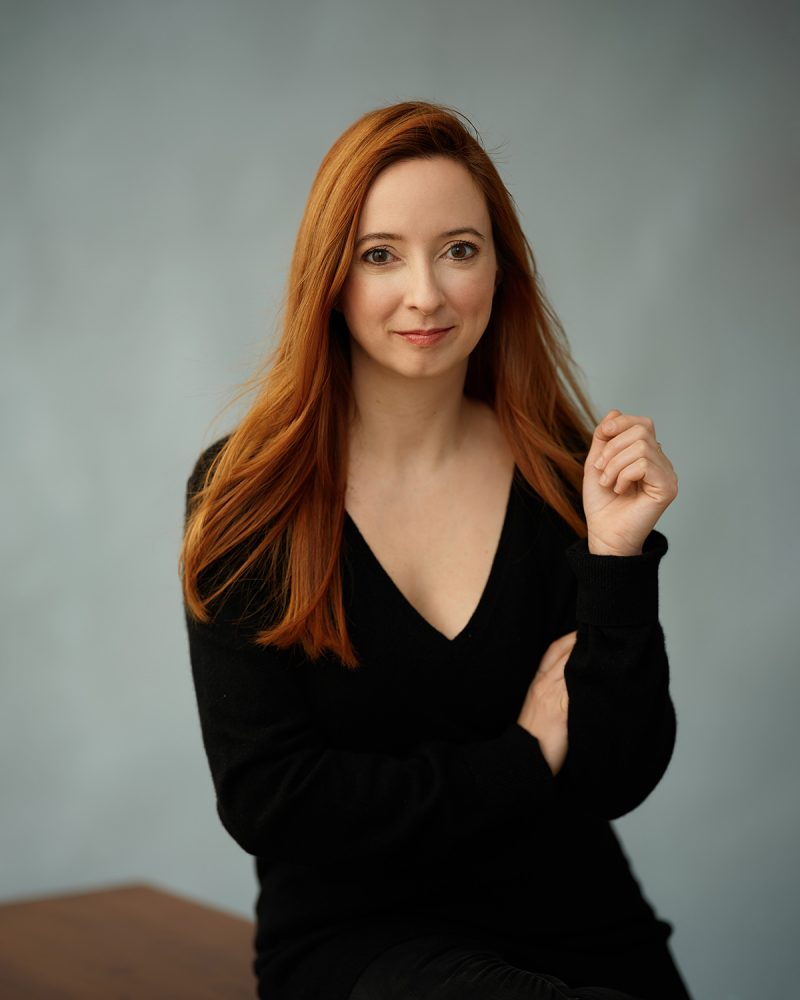 Montreal-musician-portrait-red-hair-black-sweater-sitting-on-wooden-table-by-nadia-zheng